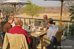 People eating at outside dining area where they can view the game preserve at the Stanley and Livingstone Hotel