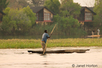 Fisherman poling a mokoro canoe in the Chobe River