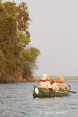 African safari guide and tourists paddling a canoe on the Zambezi River
