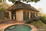 Man entering a luxury suite with a plunge pool on the patio of the Royal Zambezi Lodge