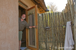 Man opening door to three-sided exterior shower at the Royal Zambezi Lodge