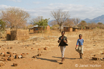 Girls walking by small brick buildings  in the Chiawa Cultural Village