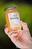 Man's hand holding a jar of artisanal Beek's honey made in Seattle, Washington