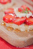 Sliced strawberries on bread with goat cheese and honey drizzled over it, with a sprig of rosemary on top, resting on a wooden cutting board