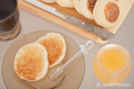 Homemade sourdough english muffins cut and covered with honey, with a plastic honey dipper resting on the plate, a honey jar to the right of the plate, a mug of coffee to the left of the plate, and a cutting board, knife and more english muffins above the plate