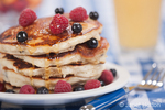 Blueberry pancakes with artisanal Misty Mountain Mixed Wildflower honey being poured onto them, and blueberries and raspberries on and around them, resting on a white plate, on a blue checkered tablecloth, with a glass of orange juice and a small bowl of cantalope, and berries in the background