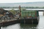 Crane loading barge with scrap metal