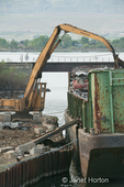 Crane loading barge with scrap metal