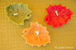 Three leaf-shaped pure beeswax candles of varying colors for sale at a farmer's market