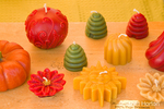 A variety of pure, beeswax candles molded in various shapes for sale at a farmer's market