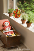 Family room with three clay pots of herbs (Greek Oregano, Silver Posie Thyme and Berggarten Sage) on a windowsill, autumn leaves decorative glass plate, antique handmade cradle with a Raggedy Ann doll in it