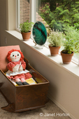 Family room with three clay pots of herbs (Greek Oregano, Silver Posie Thyme and Berggarten Sage) on a windowsill, swordfern decorative glass plate, antique handmade cradle with a Raggedy Ann doll in it