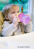 Young toddler girl (15 months old) drinking from her sippy cup, while sitting in a high chair