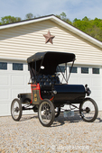 Front view of a replica 1901 Curved Dash Oldsmobile in front of a garage door