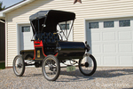 Side view of a replica 1901 Curved Dash Oldsmobile in front of a garage door