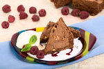 Brownies with scoop of ice cream and raspberries on a striped plate with other brownies and raspberries in the background, sitting on a blue napkin