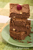Stack of four brownies on a green plate with a raspberry on top sitting on a green checkered placemat