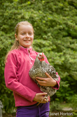 Eleven-year old girl holding a Silver-laced Wyandotte chicken