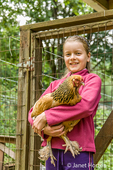 Eleven-year old girl holding an Ameraucana hen in front of a chicken coop 