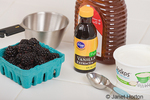 Ingredients to make blackberry popsicles, including blackberries, greek-style yogurt, honey and vanilla, along with a measuring spoon and cup, sitting on a white kitchen countertop