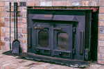 Buck wood-burning stove inset into a brick fireplace, with fireplace tools next to it