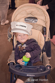 21 month old boy in a stroller, wearing a paper train engineer hat, on-the-go at a train show