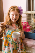 Eight-year old girl pouring guinea pig pellets into a pet food bowl
