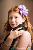 Eight-year old girl holding and cuddling her guinea pig on her shoulder