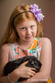 Eight-year old girl holding and cuddling her guinea pig in her arms
