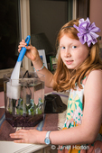Eight-year old girl cleaning the inside of her fish tank using a sponge on a handle