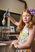 Eight-year old girl cleaning the inside of her fish tank using a sponge on a handle, with the brush out of the water draining and dripping