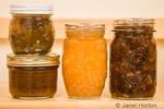 Home-canned goods on a pantry shelf, from left to right: pepper jelly on top of pear butter, peach jam and rhubarb conserve