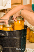 Woman placing canning jars into a rack of a hot water bath canner.