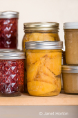 Pantry shelf of canned goods, from left to right: raspberry organic jam, red haven peaches and organic applesauce