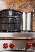 Blue canning kettle and large stainless steel stock pot being used to prepare apricot jam on a high-end stove