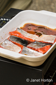 Salmon filets in a brining mixture in a ceramic dish, ready to be put into the smoker (below it) to be preserved.