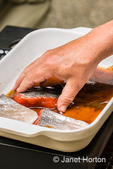 Man picking up salmon filets out of a brining mixture in a ceramic dish, to put them into the smoker (below it) to be preserved.