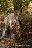 Woman turning this compost pile with a compost fork.