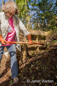 Woman turning a compost pile with a compost fork.