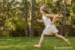Seven year old barefoot girl running in her backyard, getting ready to leap