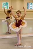 Seven year old girl in fifth position at a ballet dance dress rehearsal in a studio