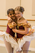 Seven year old girls hugging, showing their friendship, at a ballet dance dress rehearsal in a studio