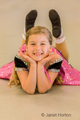 Seven year old girl posing in a jazz dance position at a jazz dance dress rehearsal in a studio