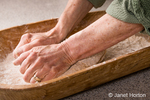 Woman kneading dough in a dough trough until it is smooth and elastic, as part of making sprouted wheat bread.