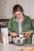 Woman adding unbleached white flour to monkey bread ingredients.