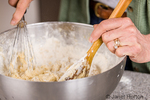 Woman stirring bread ingredients, at first using a whisk, then switching to a wooden spoon as the dough becomes thicker, as part of making monkey bread