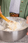 Woman stirring bread ingredients, using a wooden spoon as the dough becomes thicker, as part of making monkey bread