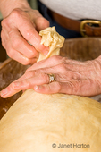 Woman pinching off golf ball-sized pieces of dough and shaping into a round ball, to make Monkey Bread.