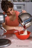 Woman pouring Naan bread dough into a bowl to rise
