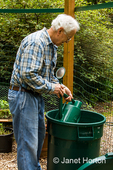 Man filling his watering can from a large garbage can of water beside his garden